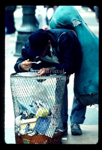 LA Street Person eating peas -Garbage can