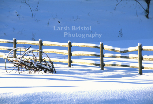 Snow Covered Fence and Wagon Wheeled Trailer